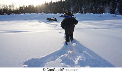 Winter fishing - Fisherman with ice screws walking on ice...