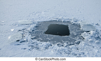 Winter fishing hole, frozen lake with snow and ice