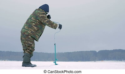 Winter fishing on river. A man drills a hole in ice. -...