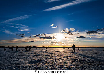 Winter fishing. Silhouette of fishermen catching fish on the icy surface of the river