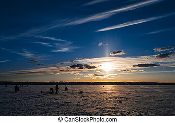 Winter fishing. Silhouette of fishermen catching fish on the icy surface of the river in background the beautiful sunrise