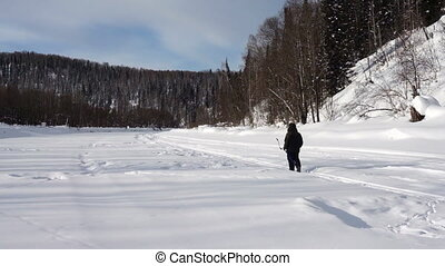 Winter fishing - The fisherman on the river drills ice