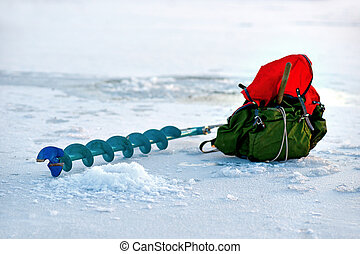 Winter fishing - Auger and backback near a newly drilled...