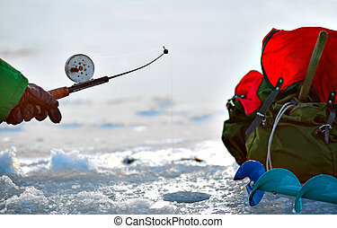 Winter fishing - Hand of person fishing in a hole in ice