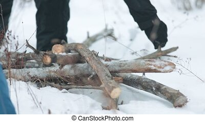 Winter forest. A person picking up the stick from the snowy...