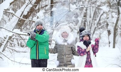 Winter forest. Cheerful children in bright clothes blow up christmas crackers