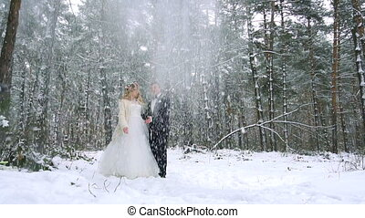 Winter forest shot of young couple having fun under snowfall. Slow motion