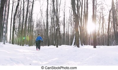 Winter forest. Young man and woman do a morning jog. Mid...