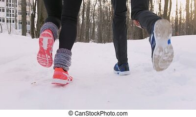Winter forest. Young man and woman jogging. Feet close up