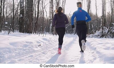 Winter forest. Young man and woman running on the trail in the morning park. Beautiful sunlight. Back view