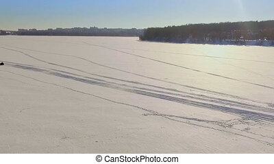 Winter fun. A trip on a snowmobile over frozen lake ice
