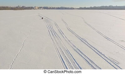 Winter fun. A trip on a snowmobile. Two guys are riding a snowmobile over frozen lake ice