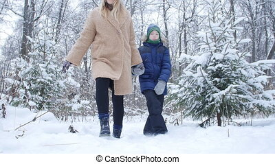 Winter Fun and Travel Concept. Mother and son walking in snowy forest