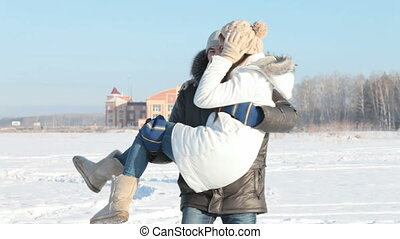 Winter fun - Boy carrying girlfriend in his arms and ...