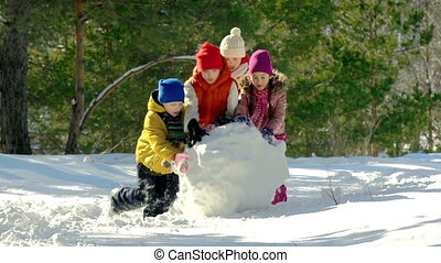 Winter Fun - Four kids busy making snowman