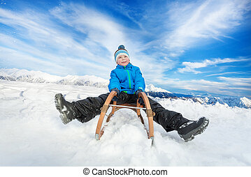 Winter fun in snow mountains boy on sledge