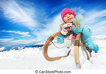 Winter fun in snow mountains girl on sledge
