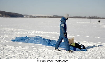 Winter fun. People on the frozen lake are engaged in paragliding and winter fishing