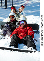 Winter fun - Portrait of happy friends snowboarding during...