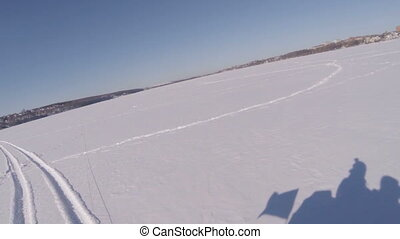 Two guys ride a snowmobile on a frozen lake. Shadows of the guys in the snow