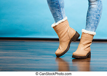 Winter fur boots on female feet