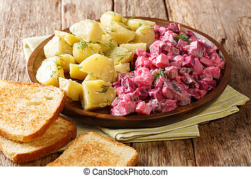 Winter German herring salad with vegetables and a side dish of boiled potatoes close-up in a plate. horizontal
