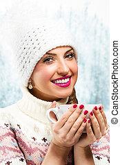 Winter girl drinking warm beverage