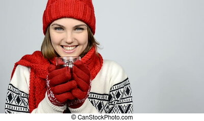 Winter girl in red warm knitted hat and scarf holding cup of tea