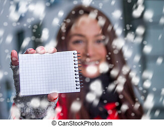 winter girl in the snow with a plain notice sheet