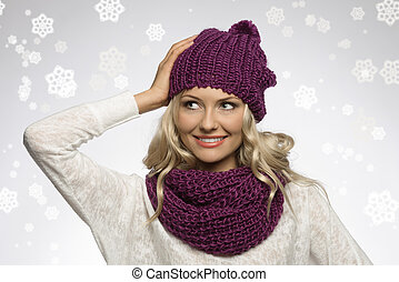 winter girl in white with purple hat and fake snow - between...