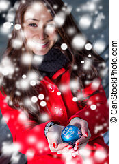 winter girl with a christmas sphere in the snow