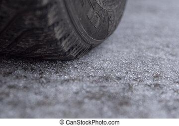 Winter hail on the road. Car wheel.