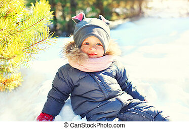Winter happy smiling child playing in snow
