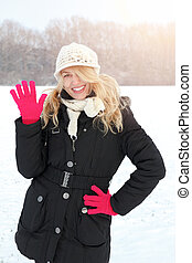 winter happy woman in snow looking up at camera and waving