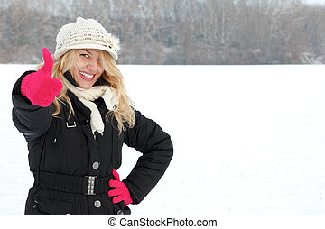 happy woman in snow looking up at camera with thumb up