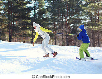Winter happy young smiling mother with son child go skiing having fun in forest at mountain