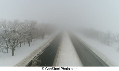 Winter highway in the fog. Aerial video - Flying over the...