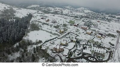 Winter hills slopes strewn with snow. Snowy village. Aerial view