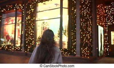 Winter holiday season. Christmas, New Year concept. Woman by illuminated showcase on city street.