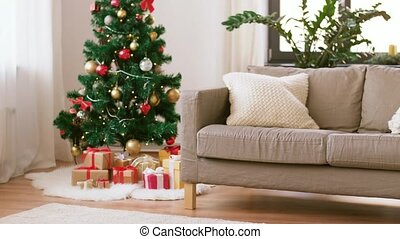 christmas tree, gifts and sofa at cozy home - winter...