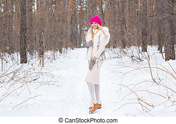 Winter, holidays and people concept - Beautiful young woman in winter park with snow