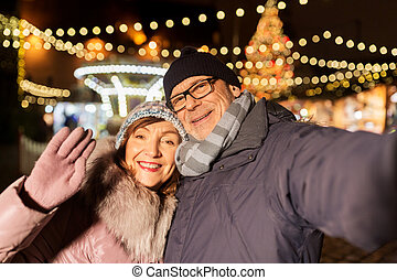 senior couple taking selfie at christmas market