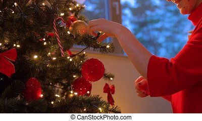 woman decorating christmas tree with ball - winter holidays...