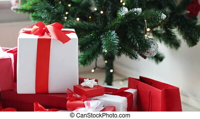 woman putting present under christmas tree - winter...