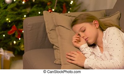 little girl sleeping on sofa near christmas tree