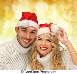 smiling couple in sweaters and santa helper hats - winter,...