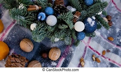 Winter holidays concept. A beautiful handmade Christmas wreath lies on a bedspread covered with snowflakes and branches of a Christmas tree.