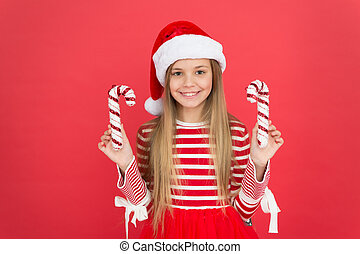 Winter holidays. Playful mood. Christmas celebration ideas. Shine and glitter. Child Santa Claus costume hat. Happy smiling face. Beautiful detail. Positivity concept. Playful baby. Christmas party