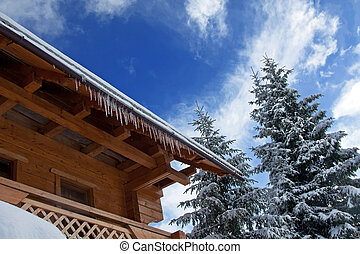 Winter house with icicles in the forest