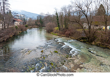 A small river in the French Savoy Area, separating the towns of Echelles and Entre-Deux-Guiers, on a winter afternoon around christmas.